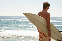 Man holding surfboard by ocean back view