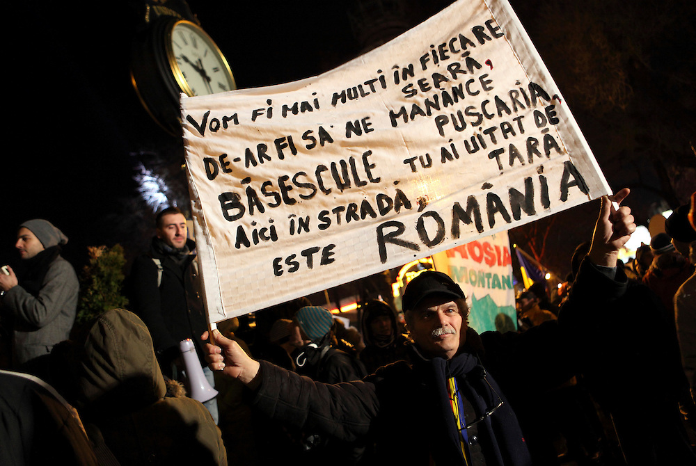 January 21st 2012, a protester holds a sign reading ''There will be more of us each night, even if we have to face jail, Basescu you have forgotten your country, here in the street this is Romania'' during a protest against Romania's government at the University square in Bucharest, Romania. Hundreds of Romanians rallied  all over the country   to protest against austerity measures, calling for president Basescu and the government to resign.