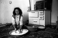 Kosovo - Pejë,  Novembre 2000. Fatima, rom askalia, vedova con nove figli, prepara il pane per la cena, abita nel quartiere rom dietro la stazione ferroviaria.