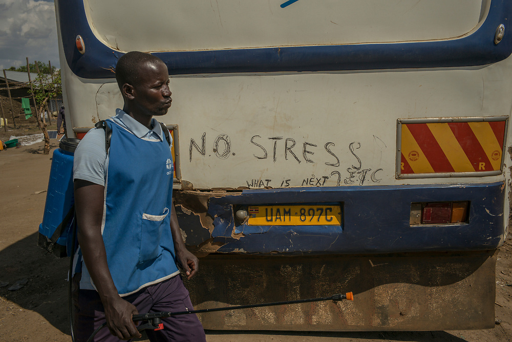 SEBAGORO, UGANDA - MARCH 22: A man walks past a bus bound for Kyangwali refugee settlement camp after spraying it with chlorine to prevent the spread of cholera in Sebagoro, Uganda on March 22, 2018. Violence in Ituri Province in northeastern Democratic Republic of Congo has displaced more than 100,000 people including approximately 40,000 refugees who have fled to Uganda. (Photo by Andrew Renneisen for The Washington Post)
