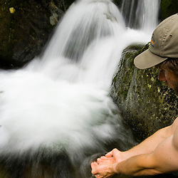 Dipping hands into Gorge Brook on Mount Moosilauke in New Hampshire's White Mountain National Forest.
