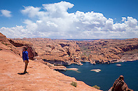 A hiker takes in the view of Lake Powell below Hole-in-the-Rock in the Glen Canyon National Recreation Area, Utah