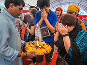 07 SEPTEMBER 2014 - BANGKOK, THAILAND: People receive blessings during the Ganesh Festival at Central World in Bangkok. Ganesh Chaturthi, also known as Vinayaka Chaturthi, is a Hindu festival dedicated to Lord Ganesh. It is a 10-day festival marking the birthday of Ganesh, who is widely worshiped for his auspicious beginnings. Ganesh is the patron of arts and sciences, the deity of intellect and wisdom -- identified by his elephant head. The holiday is celebrated for 10 days, in 2014, most Hindu temples will submerge their Ganesh shrines and deities on September 7.     PHOTO BY JACK KURTZ