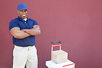 Portrait of a muscular African American man standing with arms crossed and handtruck over colored background