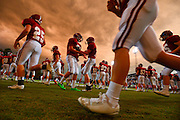 Gary Cosby Jr./Decatur Daily     Hartselle players warm up for their game with Cullman beneath a beautiful, stormy sky in J.P. Cain Stadium in Hartselle Friday night.