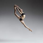 Contemporary ballet dancer, Natasha Sheehan, jumping in the studio on a gray background. Photograph taken in San Francisco by Rachel Neville.