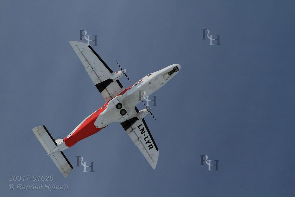 Regularly-scheduled Lufttransport Dornier Do 228 airplane flies above Hamnerabben Airport in Ny-Alesund on Spitsbergen island in Kongsfjorden; Svalbard, Norway.