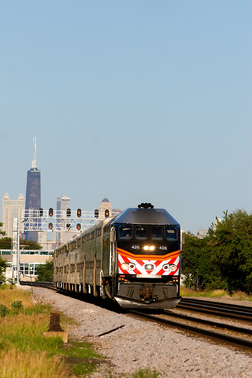 A Metra commuter train rushes west away from the skyline of Chicago, IL during a summer afternoon rush hour.