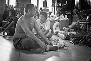 """Mar. 29, 2010 - NAKORN CHAI SRI, THAILAND:  People with their offerings wait to be tattooed at Wat Bang Phra about 30 miles from Bangkok in Nakhon Pathom province. The temple is famous for its tattooing monks who give people """"Sak Yent"""" tattoos, a form of sacred tattooing practiced in Southeast Asian countries including Cambodia, Laos, and Thailand. The typical tattoo takes about 3,000 strikes to complete. When ready to begin, he will dip the tip of the needle into a mix of oil, probably palm oil, Chinese charcoal ink, and possibly snake venom. The monk dips the needle into the ink about every 30 seconds.  PHOTO BY JACK KURTZ"""