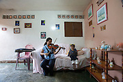 "Viola player Andri at home, playing a little music for her little niece. She learns in Jose? Marti? Bolivarian school at the Barrio Sarria, one of Caracas' poor quarters, home to the ""Nucleo Sarria of the ""Fundacion del Estado para el Sistema Nacional de las Orquestas Juveniles e Infantiles de Venezuela"" (FESNOJIV, National Network of Youth and Children Orchestras of Venezuela). This organization is also known as El Sistema, is a publicly financed private-sector music-education program in Venezuela, originally called Social Action for Music, founded 1975 by Venezuelan economist and amateur musician Jose? Antonio Abreu."