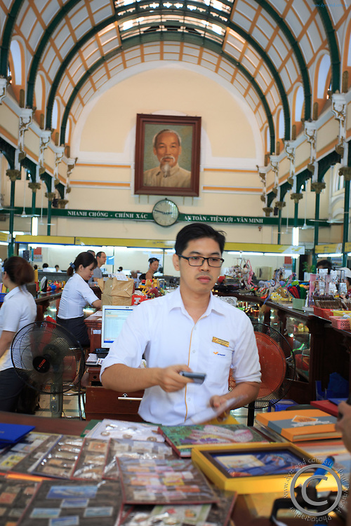 A post office worker serves a customer at the Central Post Office in Ho Chi Minh City, Vietnam