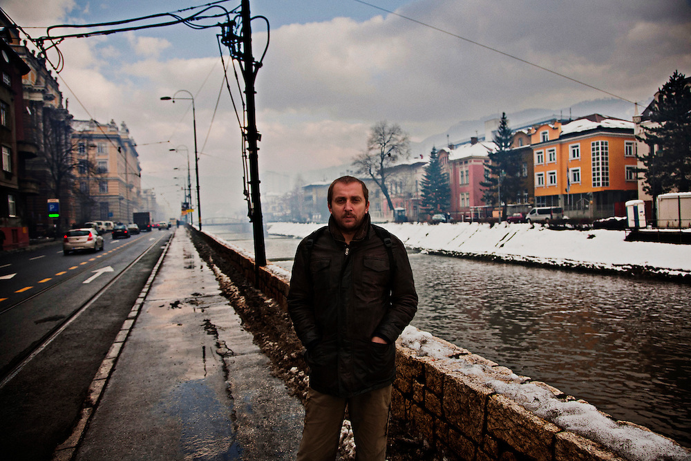 "Poet and writer Faruk Sehic along the banks of the Miljacka river in the center of Sarajevo. He fought from 1992-1995 in the Bosnian National Army in Bihac before moving permanently to Sarajevo where he became a journalist and writer.  He writes a column for one of the most respected weekly newsmagazines where he profiles individual Bosnians from around the country. The popular series has gained him a respect and notoriety in the country. His poetry is also highly regarded; his book ""Street Epistles"" won a major prize in Belgrade and was published in an edition with the original Bosnian with English translations side by side."