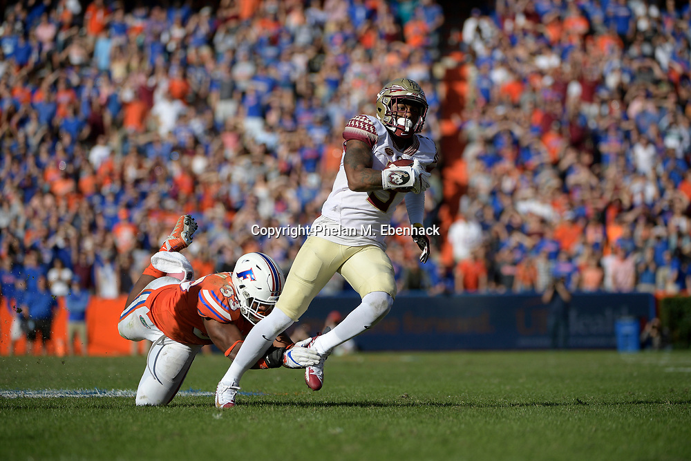 Florida State wide receiver Ermon Lane (5) catches a 39-yard pass in front of Florida linebacker David Reese (33) during the second half of an NCAA college football game Saturday, Nov. 25, 2017, in Gainesville, Fla. FSU won 38-22. (Photo by Phelan M. Ebenhack)