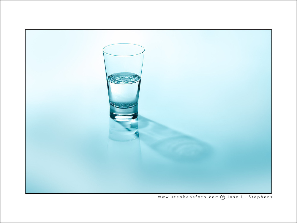 Still life photography representing the concept of Half Full / Half Empty glass of water.