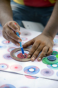 KOCHI, INDIA - 3rd September 2019 - A spirograph seller demonstrates how to use the geometric drawing toy for potential buyers along Fort Kochi Beach and Seafront Promenade, Cochin, Kerala, Southern India