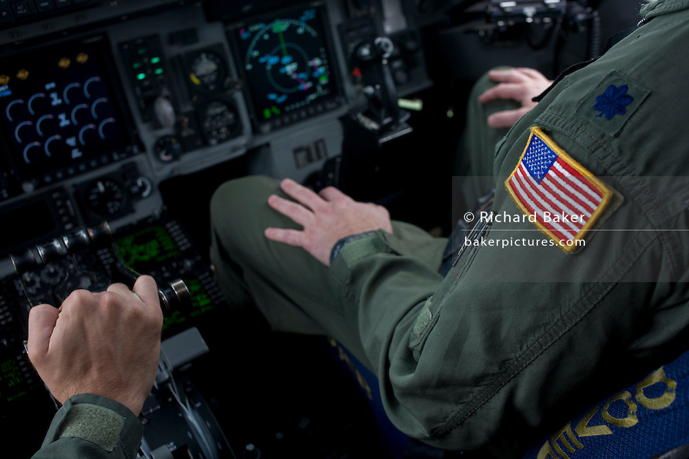 A pilot of the US Air Force holds the throttle levers in the cockpit of a C-17 transport jet at the Farnborough Air Show, UK.
