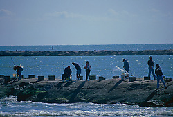 Stock photo of a group of people fishing off of a pier in Galveston