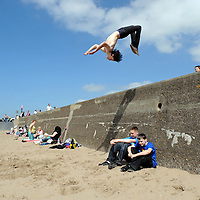 Holidaymakers and local flock to the beach at Ayr as Scotland prepares for a blistering weekend of sunny weather. Greg Harris aged 16 from Birmingham practises Parkour off the seawall.