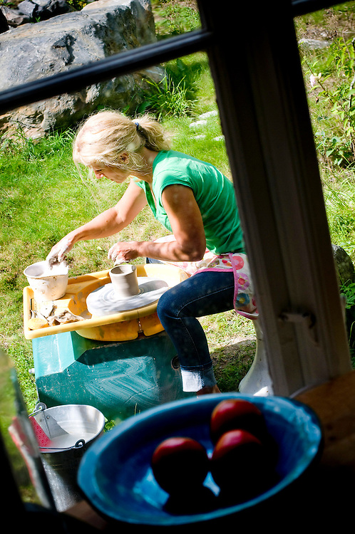 Susanna Zacke photographed through the kitchen window of her summer home on the island Storholmen, outside Stockholm, while she is making clay pottery....Photographer: Chris Maluszynski /MOMENT