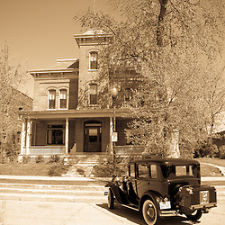"""Crown Point Indiana Lake County jail with a Ford Model A antique car parked in front. Photo is Sepia toned to give old vintage appearance. In 1934 John Dillinger escaped from the Lake County jail in this building. In 2008 Universal Studios filmed parts of the movie Public Enemies with Johnny Depp. The jail is open to the public for tours and goes past Dillinger's cell and also where filming was done. Crown Point is located in Northwest Indiana with a population of over 37,000. Crown Point and Lake County are about 50 miles from Chicago and are considered part of the """"Chicagoland"""" area. Crown Point has a traditional small town America feel with a main street consisting of the old Lake County Courthouse surrounded by numerous small businesses, known as """"the square"""", including a theater, ice cream shop, antique stores, and restaurants."""