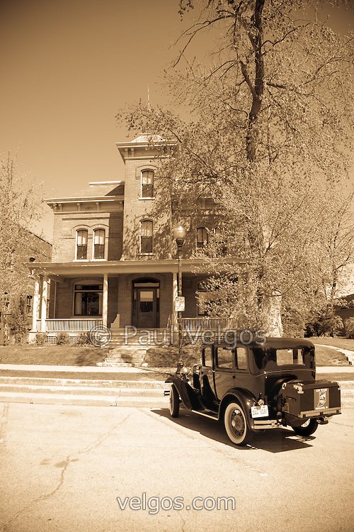 "Crown Point Indiana Lake County jail with a Ford Model A antique car parked in front. Photo is Sepia toned to give old vintage appearance. In 1934 John Dillinger escaped from the Lake County jail in this building. In 2008 Universal Studios filmed parts of the movie Public Enemies with Johnny Depp. The jail is open to the public for tours and goes past Dillinger's cell and also where filming was done. Crown Point is located in Northwest Indiana with a population of over 37,000. Crown Point and Lake County are about 50 miles from Chicago and are considered part of the ""Chicagoland"" area. Crown Point has a traditional small town America feel with a main street consisting of the old Lake County Courthouse surrounded by numerous small businesses, known as ""the square"", including a theater, ice cream shop, antique stores, and restaurants."