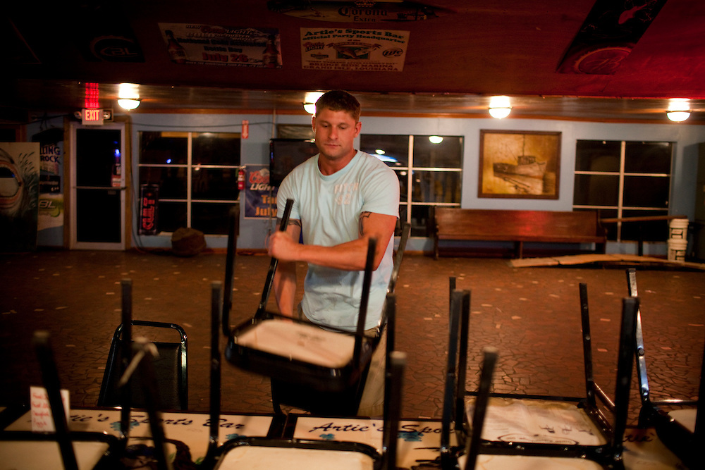 Josh Ketchum, 28 a boyfriend of a bartender at Arties Sports Bar helps clean up in Grand Isle, LA on June 23, 2010 where oil has reached land and killed the tourist industry. Manager Frankie Marullo said the bar would be packed with tourists during this time of the year but since the spill business has been slow and closes early.