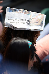 © Licensed to London News Pictures. 24/06/2014. London, UK . A fan uses Metro as a sun hat at the Wimbledon Tennis Championships 2014. Photo credit : Mike King/LNP