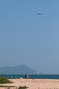 A jet airplane comes in for a landing over Sand Island on Oahu.