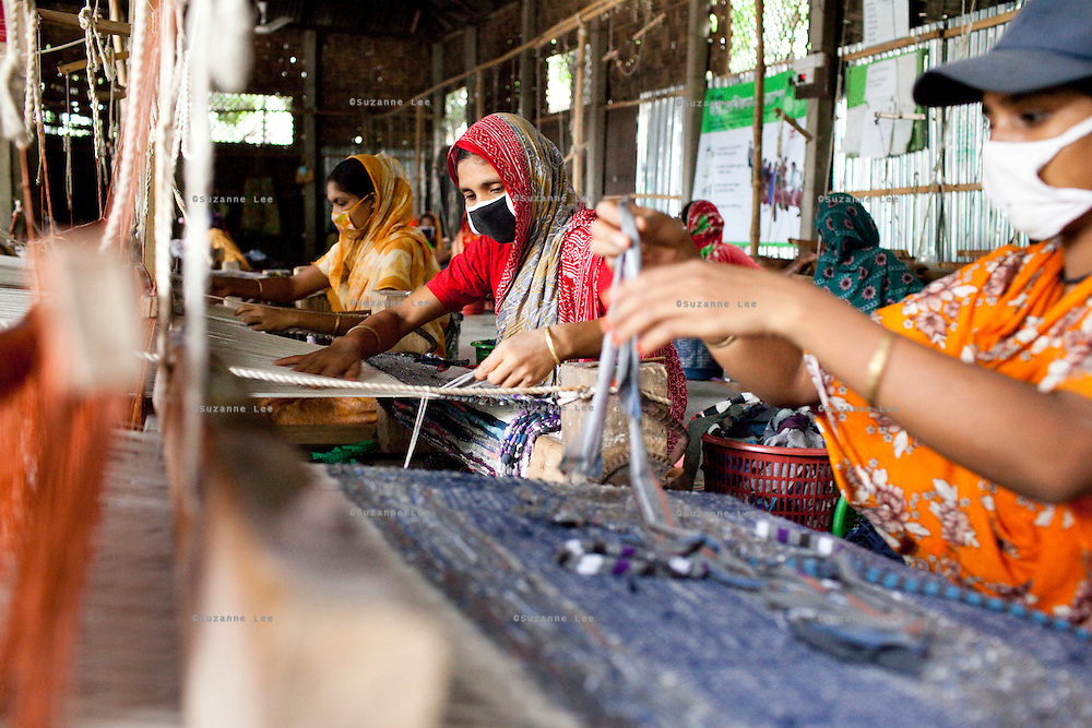 (L-R) Mosiammat Rahimah Begum (yellow sari), Mosammat Reshona Khatun (center, red sari), and Mossammat Dulali Begum (grey hat) work on their rugs at the Mornia Kik Rug Factory in Doani Villlage, Haragach Upazila, Rangpur, Bangladesh on 19th September 2011 where they work alongside 25 rural village women making rugs for German textile discounter Kik. Over 400 women have been economically empowered through the CARE Bangladesh WONDER Project that was completed recently. The WONDER Project's goals were to create sustainable income and employment opportunities for extremely poor women by training them in rug production for export. The women now earn about 4000 Bangladeshi Taka per month. The WONDER Project has now moved into a new phase that focusses on general healthcare, workplace safety and nutritional training and awareness programs. Photo by Suzanne Lee for The Guardian