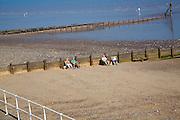 People sitting on sandy beach by wooden groynes, Hornsea, Yorkshire, England