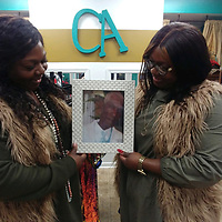 Twin sisters, Latoya Straughter and Latasha Campbell hold a photo of their late father, Charles Harris, at their Aberdeen Main Street store, Charlee's Angels Unique Boutique.