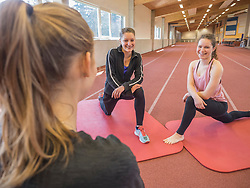 Young women practicing yoga in athletics hall on tartan track, Offenburg, Baden-Wuerttemberg, Germany