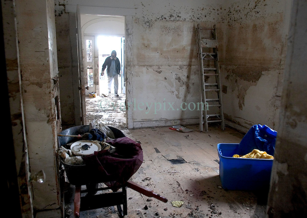 21 December 05. New Orleans, Louisiana.  Post Katrina aftermath.<br /> Armand Devezin clears his grandfathers' devastated, mould filled house in the 9th Ward long after the  flood from Hurricane Katrina subsided. The house has only recently been refurbished and has seen water to the ceilings before when Hurricane Betsy hit in the 1960's.<br /> Photo; ©Charlie Varley/varleypix.com