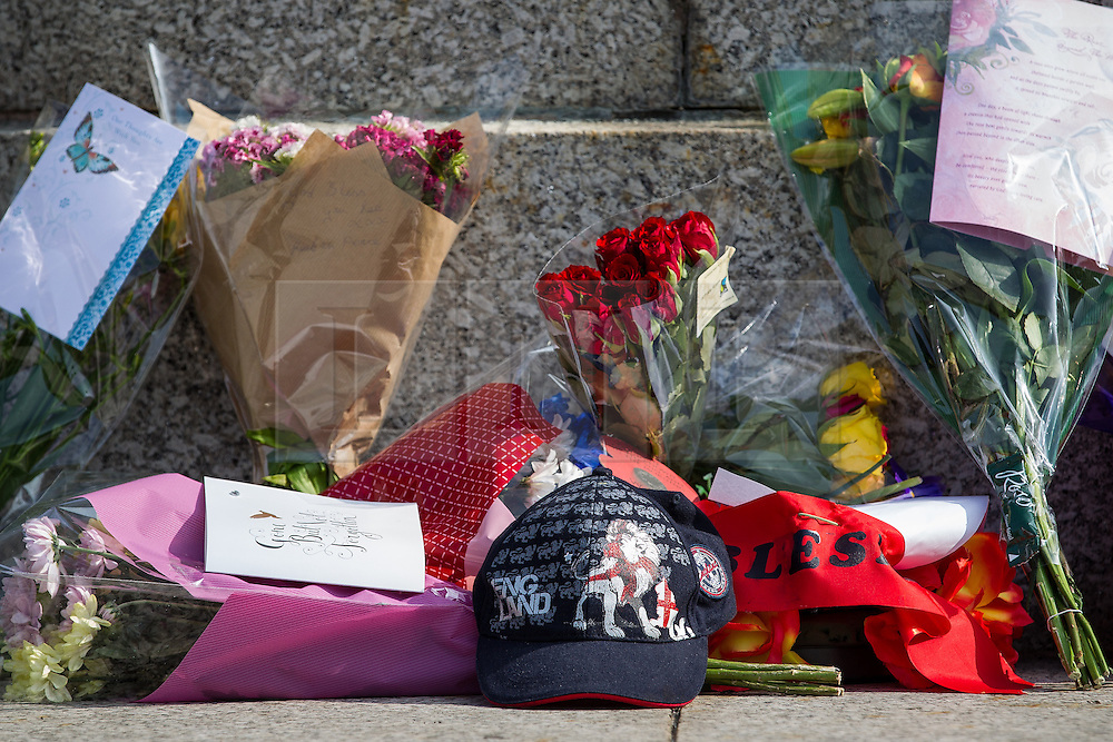 © Licensed to London News Pictures . 12/07/2013 . Bury , UK . Flowers and tributes outside the church  . The funeral for Fusilier Lee Rigby at Bury Parish Church in Bury town centre today (Friday 12th July 2013) , watched by 100s of people . Fusilier Rigby's coffin was held in Bury Parish Church overnight , watched over by an honour guard of soldiers from the 2nd Battalion Royal Regiment of Fusiliers ( 2RRF ) . Rigby was brutally murdered in Woolwich , London on 22nd May 2013 . Photo credit : Joel Goodman/LNP