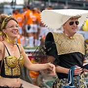 NLD/Amsterdam/20180604 - Gaypride 2018, man en vrouw in goudenkleding, man in volendamse klederdracht van rubber