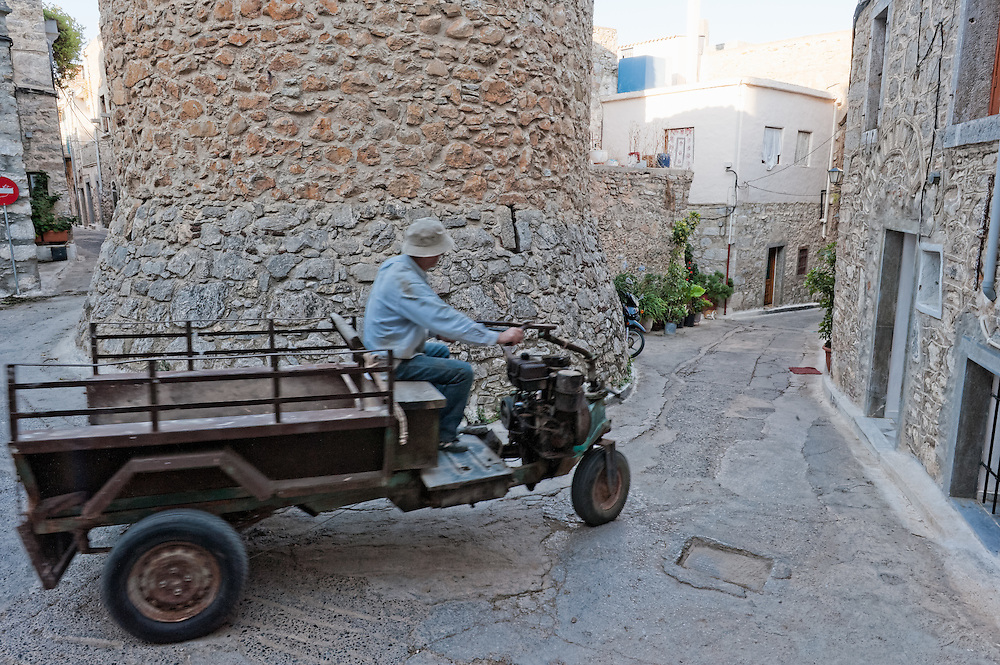 A man drives his tricycle through the narrow alleys of the medieval village of Mesta, Chios, Greece