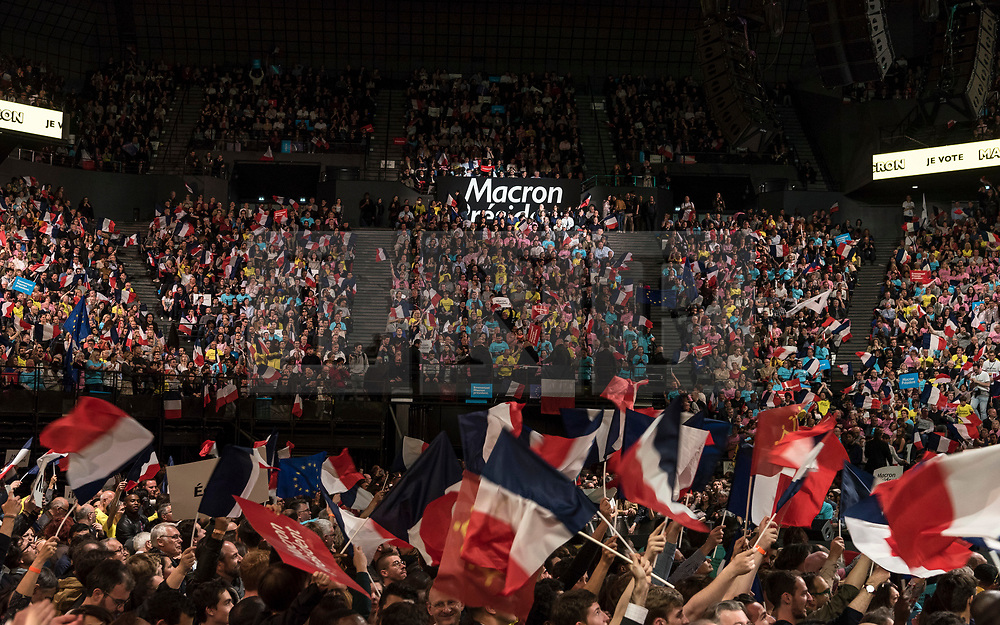 © London News Pictures. 17/04/2017. Paris, France. Supporters wave flags and hold up signs as French Presidential Candidate Emmanuel Macron addresses voters  at the Accorhotels Arena 6 days before the first round of presidential elections in France. Photo credit: Karine Pierre/LNP