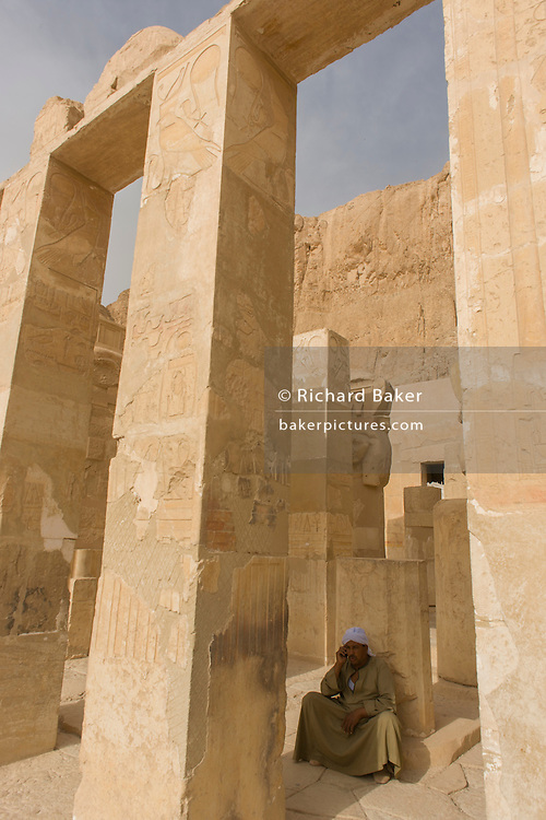 """A local guide at the ancient Egyptian Temple of Hatshepsut near the Valley of the Kings, Luxor, Nile Valley, Egypt. The Mortuary Temple of Queen Hatshepsut, the Djeser-Djeseru, is located beneath cliffs at Deir el Bahari (""""the Northern Monastery""""). The mortuary temple is dedicated to the sun god Amon-Ra and is considered one of the """"incomparable monuments of ancient Egypt."""" The temple was the site of the massacre of 62 people, mostly tourists, by Islamists on 17 November 1997."""