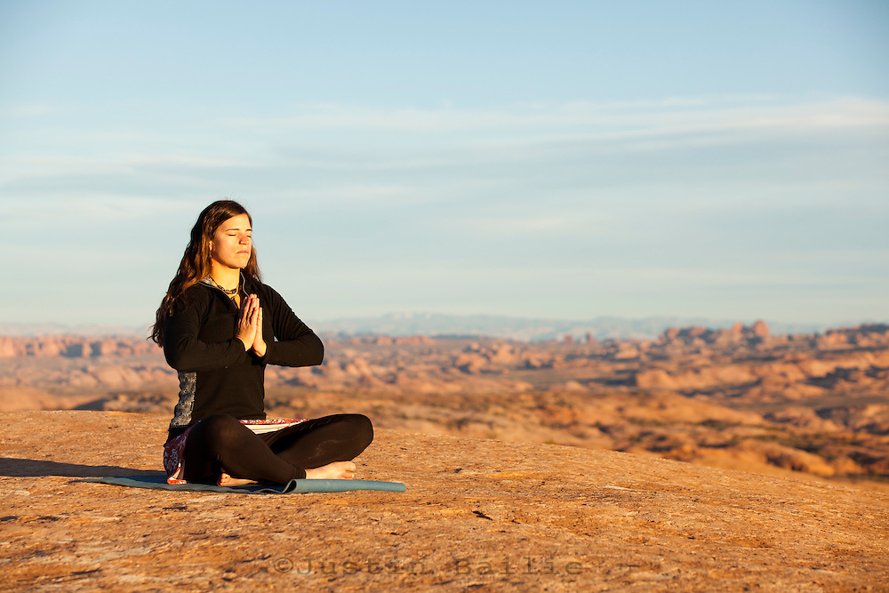 Young woman doing yoga in Moab, UT.