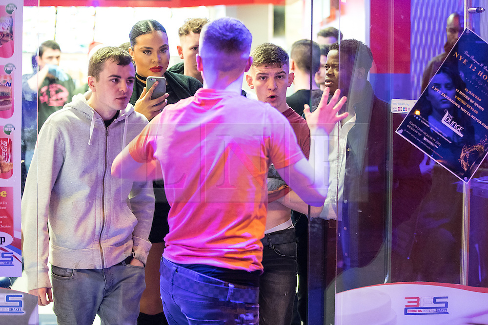 """© Licensed to London News Pictures . 24/12/2016 . Manchester , UK . A fight breaks out inside a takeaway on Withy Grove . Revellers out in Manchester City Centre overnight during 2016's second """" Mad Friday """" , named for historically being one of the busiest nights of the year for the emergency services in the UK . Photo credit : Joel Goodman/LNP"""
