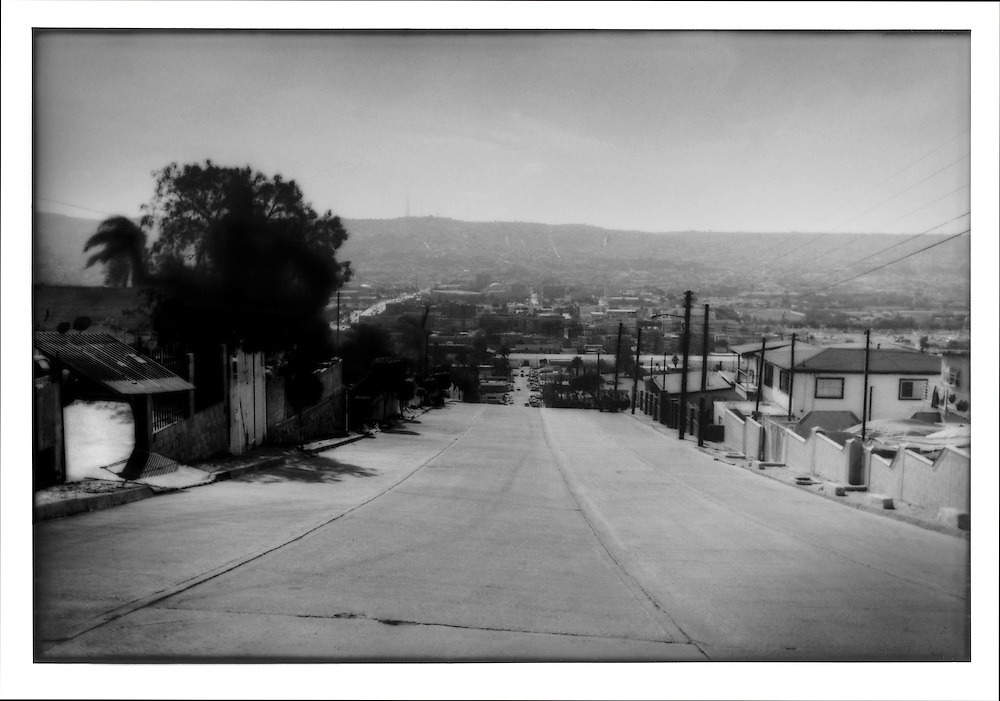 Residential section of Tijuana.  Few trees rise from gardens, many sealed with concrete above houses in Colonia Libertad, Tijuana, Baja California, Mexico.