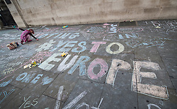© Licensed to London News Pictures. 21/06/2016. London, UK. A woman adds to chalked Yes to Europe slogans on the pavement at a Remain campaign event in Trafalgar Square organised via Facebook. There are only two full days of campaigning ahead of the UK EU referendum taking place on Thirsday 23rd June, 2016. Photo credit: Peter Macdiarmid/LNP