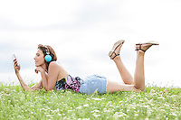 Profile shot of woman listening to music through cell phone using headphones while lying on grass against sky
