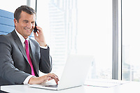 Smiling mature businessman talking on cell phone while using laptop in office