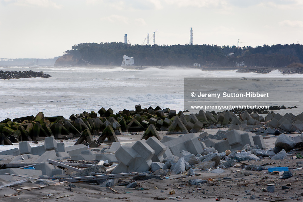 Within sight of the crippled Fukushima Daiichi nuclear plant (mast-like structures on horizon of pic) the police search Ukedo beach for bodies of tsunami victims, within the evacuated, and now uninhabited 20km exclusion zone around Fukushima Daiichi nuclear plant, in Namie, Japan, on Monday 27th February 2012..The exclusion zone used to be home to approximately 73,000 people, but all have been evacuated by the government and are now restricted from returning home due to high levels of radiation contamination from the explosions at the TEPCO owned Fukushima Daiichi nuclear plant, following the earthquake and tsunami of  March 11th 2011..Due to the towns and zone being uninhabited the police patrol to prevent crime and theft from unoccupied properties and businesses.