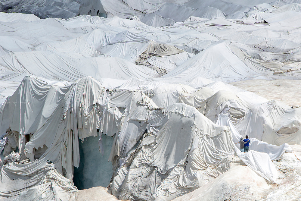 Two tourists at the entrance of the Rhone Glacier Ice tunnel. Huge fleece blankets cover parts of the Rhone Glacier in Switzerland in an attempt to stall the inevitable melting of the snow and ice. After a winter with record amounts of snow, most of it was gone when this image was taken on July 14th 2018, exposing the darker ice. The Rhone Glacier now melts more than 70 centimeters in thickness every week in the summer months. Between 1996 and 2006, an estimated 0.9 billion cubic metres of water melted yearly from the Swiss glaciers. That number is likely much higher today. Switzerland just had the hottest July since 1864, it has the lowest rainfall since 1921, and the rivers are running at record low levels. The covering of the glacier is the idea of Philipp Carlen, who owns and operates an ice cave at the mouth of the glacier. The glacier is still melting, but by covering it with blankets, he is able to attract tourists who are coming to see the dying glacier.