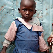 A young school child in front of the gulf plate primary school in Kibera slum, Kenya