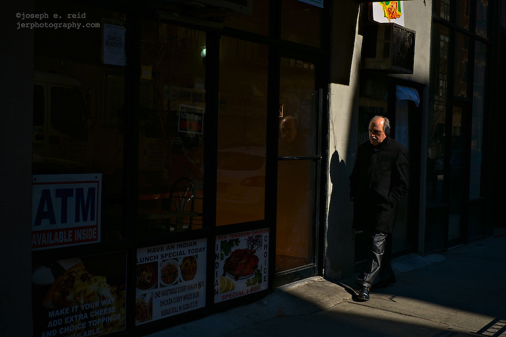 Man walking past curry shop, New York, NY, US