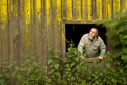 A mature man looks out a barn window at the sky with a look of concern on his face.