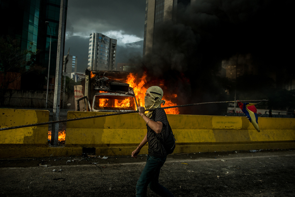 "CARACAS, VENEZUELA - MAY 27, 2017:  An anti-government protester of ""The Resistance""  during a lull in fighting as an industrial sized truck that protesters highjacked and used as a roadblock after taking over the main highway that runs through Caracas, burns in the background.  The streets of Caracas and other cities across Venezuela have been filled with tens of thousands of demonstrators for nearly 100 days of massive protests, held since April 1st. Protesters are enraged at the government for becoming an increasingly repressive, authoritarian regime that has delayed elections, used armed government loyalist to threaten dissidents, called for the Constitution to be re-written to favor them, jailed and tortured protesters and members of the political opposition, and whose corruption and failed economic policy has caused the current economic crisis that has led to widespread food and medicine shortages across the country.  Independent local media report nearly 100 people have been killed during protests and protest-related riots and looting.  The government currently only officially reports 75 deaths.  Over 2,000 people have been injured, and over 3,000 protesters have been detained by authorities.  PHOTO: Meridith Kohut"